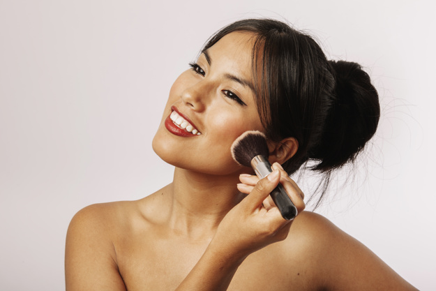 mulher jovem sorridente aplicando bb cream latika