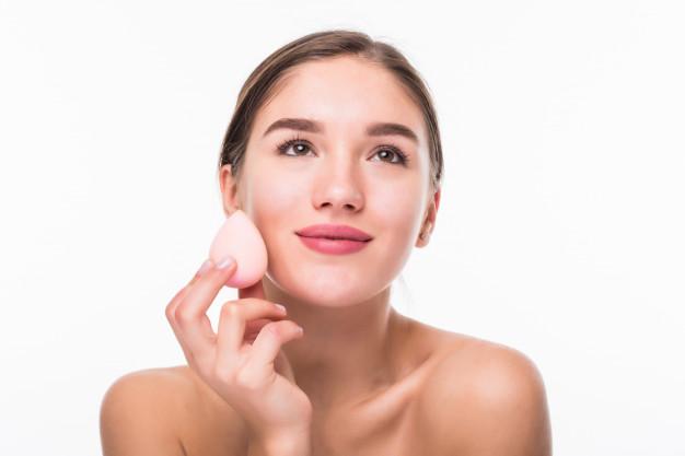 mulher-bonita-jovem-aplicando-blush-no-rosto-com-po-de-arroz-isolado-na-parede-branca_231208-1428